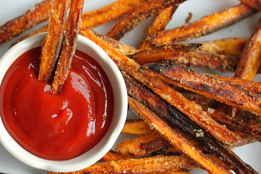 Crispy Sweet Potato Fries made with Coconut Oil dipped in ketchup