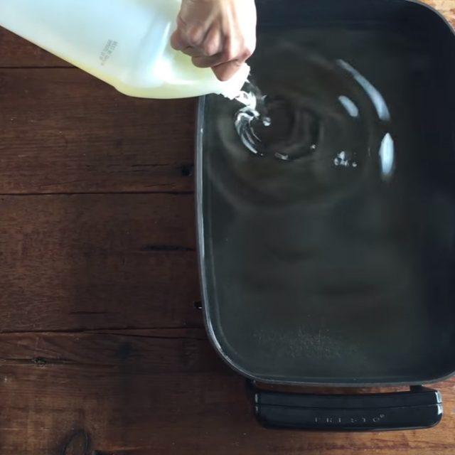 Pouring Golden Barrel Peanut Oil into a Deep Fryer